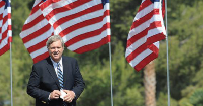 Tom Vilsack and some American flags.