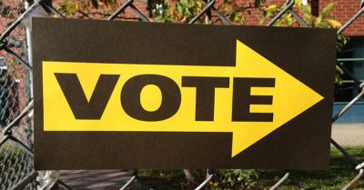 VOTE sign on a chain link fence with arrow pointing towards voting area