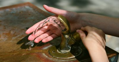 hands in a stream of water at a drinking fountain