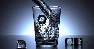 Pouring a glass of water with slightly melted ice cubes