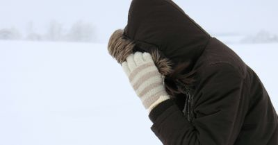 person outside in a blizzard with a furry hood and white striped gloves