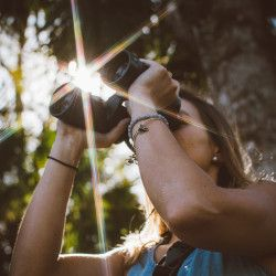 woman in a forest next to a tree holding binoculars up to her eyes