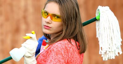 woman with protective eyewear and gloves holding a mop and spray bottle for cleaning