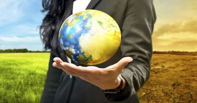 woman in a suit holding the earth in front of a dual landscape of lush greenery and desert