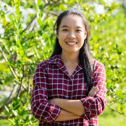 smiling farmer standing in a lime garden in a plaid shirt with her arms crossed