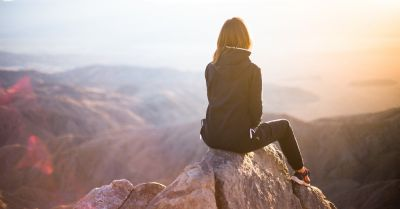 woman sitting on a mountain summit after hike looking at the landscape
