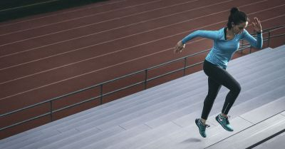 woman running up stadium stairs for health and fitness
