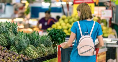 woman shopping in a grocery store in the produce section by a pineapple display