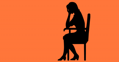 silhouette of a woman seated in a chair with her head in her hands