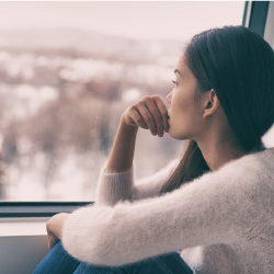 woman sitting beside a window looking out at the city skyline