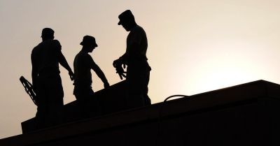 Construction workers on a rooftop at sunset
