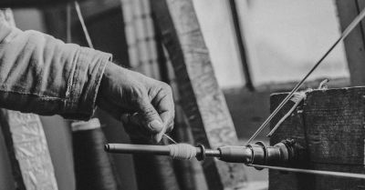 industrial factory worker spinning a thin strand of yarn thread