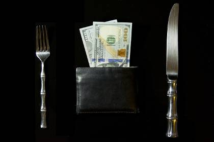 Brown wallet overflowing with cash flanked by a fork and knife