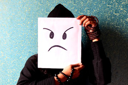 person holding a poster of an angry face
