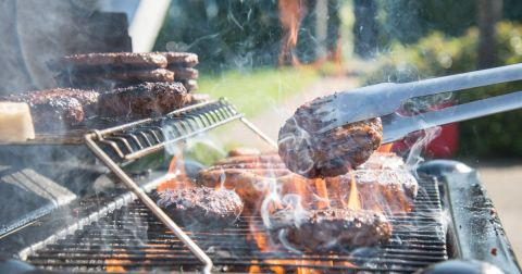 pair of tongs flipping a hamburger on an outdoor barbecue grill
