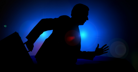 silhouette of a business man running from police car lights