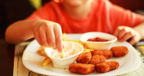 young boy eating chicken nuggets with sauces