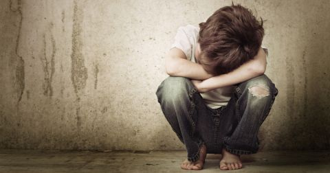young boy hanging his head in his hands while leaning against a wall alone