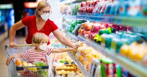 mother and young son shopping in the produce aisle of a supermarket wearing masks