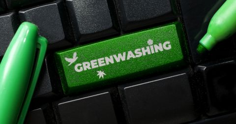 green button on a black keyboard that says GREENWASHING surrounded by green markers