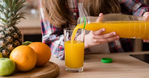 woman pouring orange juice into a glass in a kitchen by fresh fruit