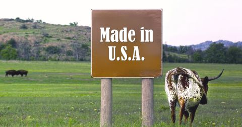 cattle grazing in a mountain landscape near a brown sign that says MADE IN USA