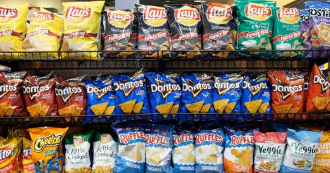 potato chips and other junk food on a store shelf in a supermarket
