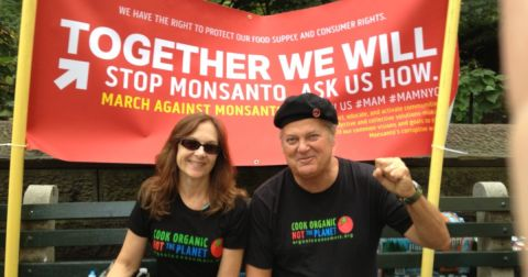 Ronnie Cummins and Katherine Paul at a protest march with signs and tshirts bearing COOK ORGANIC NOT THE PLANET