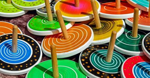 several colorful wooden toy tops