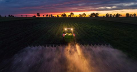tractor with its lights on spraying herbicide on farm field crops at sunset